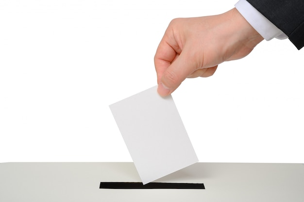 Man's hand down the ballot in the ballot box.