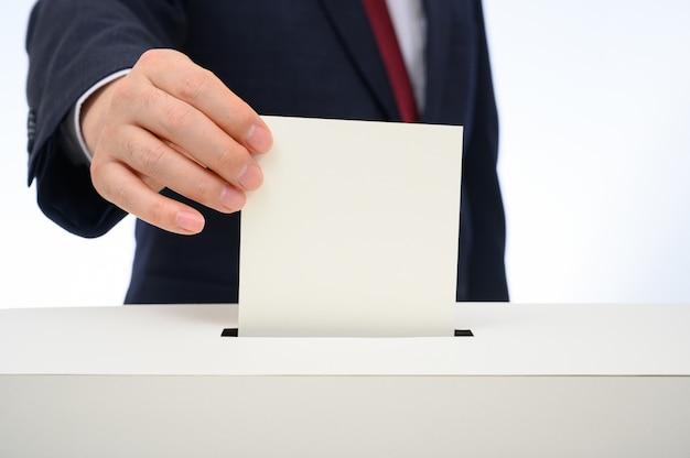 投票箱に投票用紙を入れた男の手。