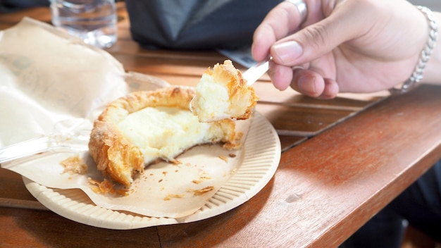 Man's hand enjoy eating a fresh baked danish .a milky cream wrapped up in the delicious crispy baked crust.