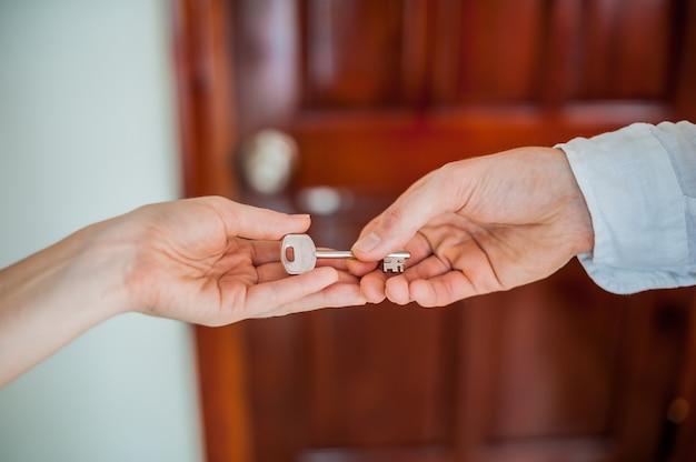 男の手は、木製のドアの背景にキーの女性を与えます。不動産の概念に対処する