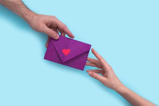 男性の手はピンクの背景に女性の手にハートの封筒を与えます