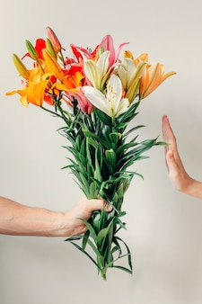 Man's hand gives bouquet of lilies flowers to girl and receives refusal