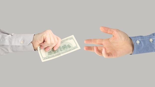 Рука человека раздает долларовые купюры другим людям. бизнес и финансы.