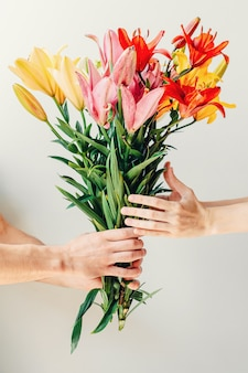Man's hand giving bouquet of flowers to woma's hand on white background