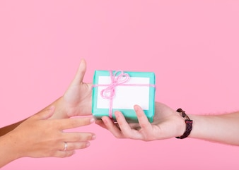 Man's hand giving gift box to other person against pink background