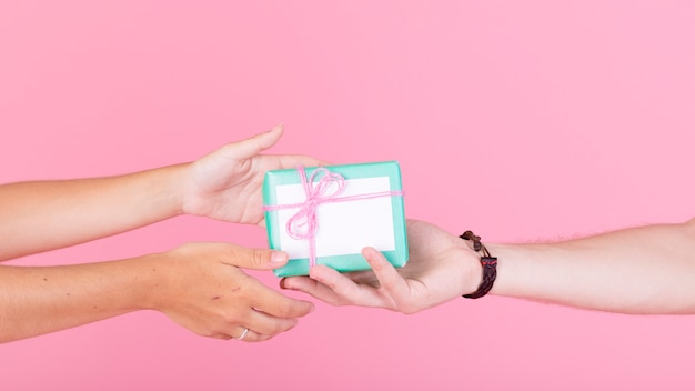 Man's hand giving gift to her woman against pink background