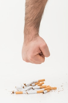 A man's hand giving punch to the broken cigarettes isolated on white backdrop
