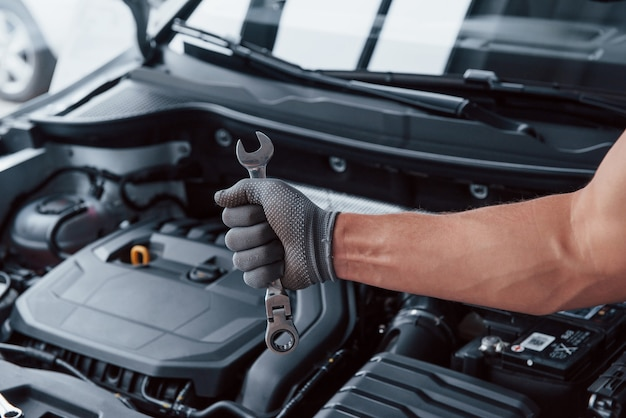 Man's hand in glove holds wrench in front of broken automobile