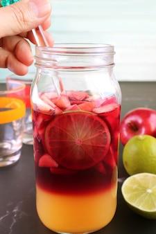 グラスボトルの赤ワインサングリアと背景のぼやけた成分を混ぜる男の手