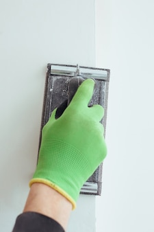 A man's hand in a green glove is grinding the wall