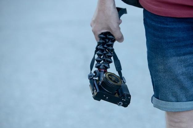 야외에서 유연한 삼각대가 있는 카메라를 들고 있는 남자의 손