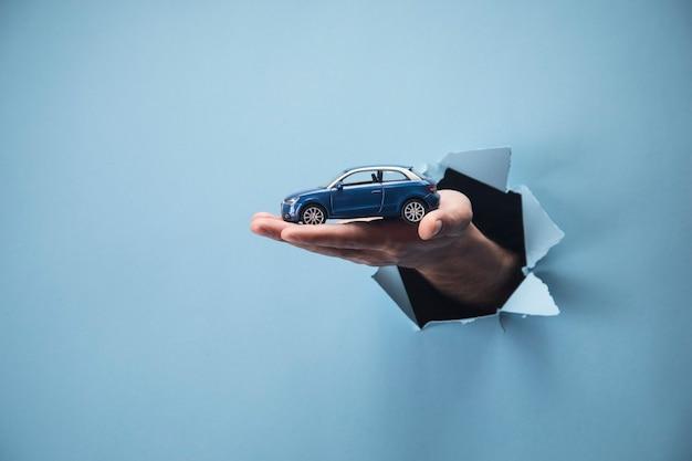 青いシーンで車を持っている男の手