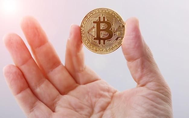 黄金のビットコインを持っている男の手