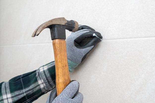 Рука человека держит молоток и прибивает стену.