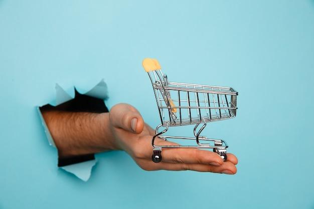 파란색 찢어진 된 종이에서 미니 식료품 쇼핑 트롤리를 들고 남자의 손.