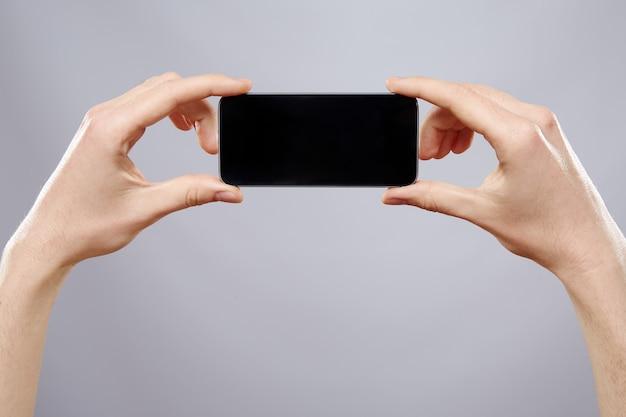 남자의 손을 잡고 휴대 전화 벽, 가까이, 비즈니스 개념, 모의, 모바일 앱, 모바일 게임.