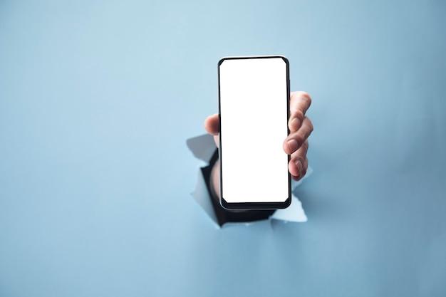 Рука человека, держащая телефон на синей сцене