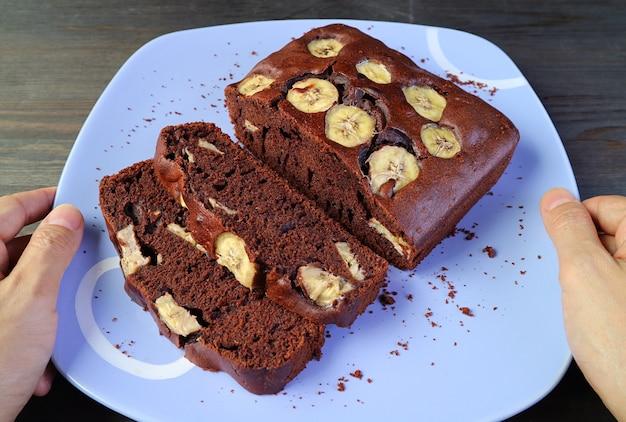 テーブルの上に置く焼きたてのダークチョコレートバナナケーキのプレートを持っている男の手