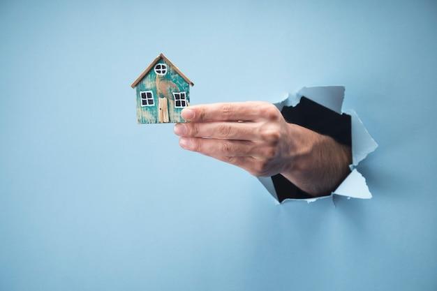 파란 장면에 작은 집을 들고 남자의 손
