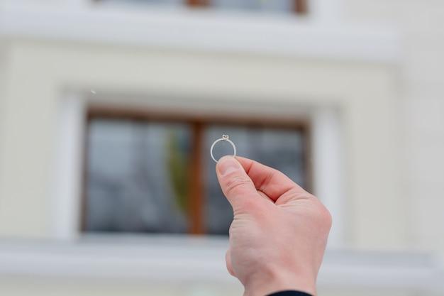 結婚指輪を持っている男の手
