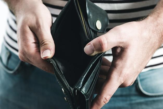 빈 검은 지갑을 들고 남자의 손입니다.