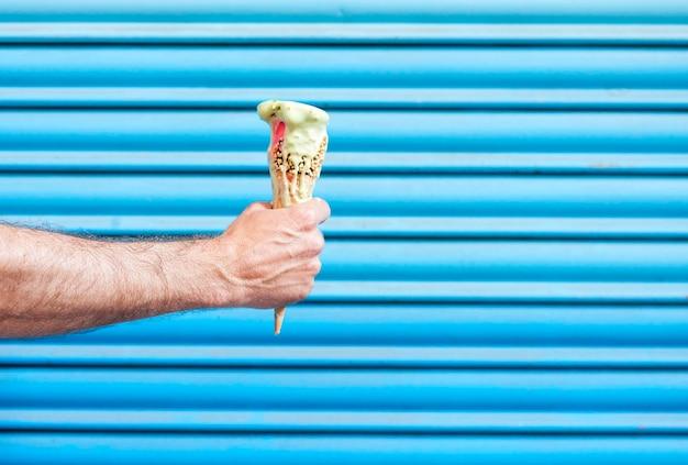 Рука человека, держащая рожок мороженого, тающий на голубом фоне