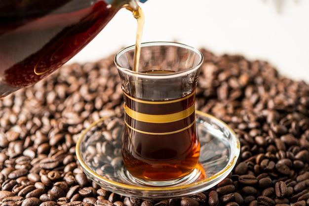 Мужская рука держит и наливает кофе в стеклянную чашку, жареные кофейные зерна