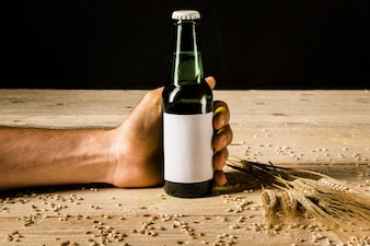 Man's hand holding beer bottle with ears of wheat on wooden surface