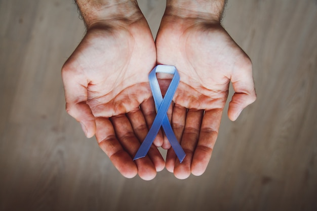 Man's hand holding a blue ribbon. prostate cancer awareness month