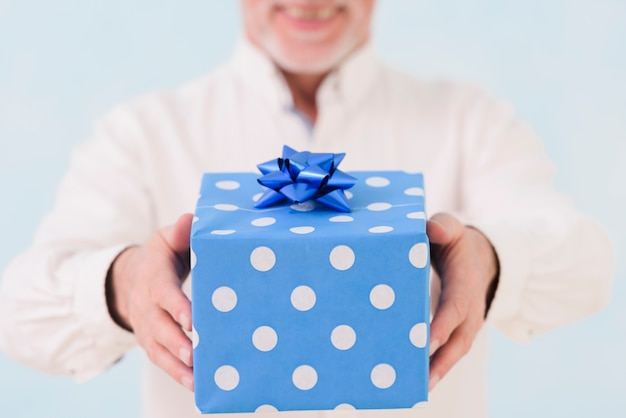 Man's hand holding blue wrapped birthday gift box