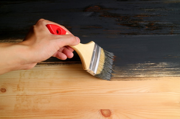 Man's hand holding brush painting wood plank with dark grey paint