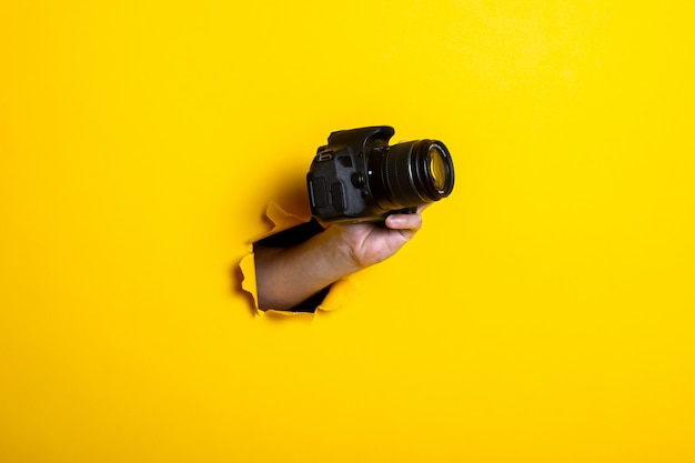 Man's hand holding a camera on a bright yellow background