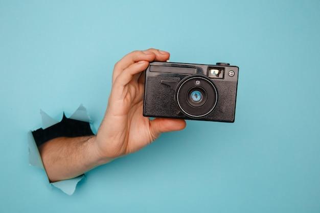 Рука человека, держащая камеру из синей рваной бумаги.