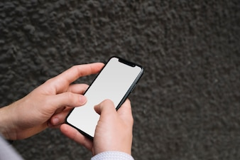 Man's hand holding cell phone with blank screen