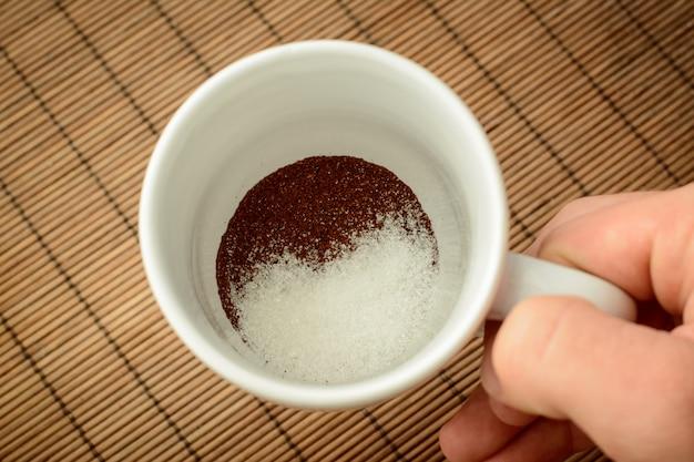 Мужская рука держит чашку с молотым кофе и сахаром на фоне коричневого бамбука