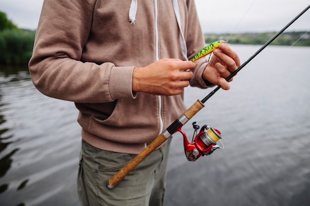 Man's hand holding fishing lure and rod