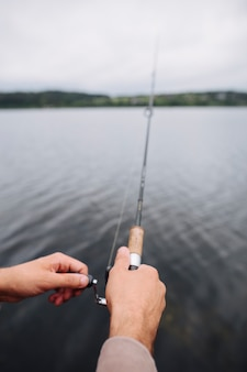 Man's hand holding fishing rod in front of lake