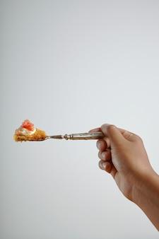 Mano di un uomo che tiene una forchetta con un pezzo di delizioso pan di spagna con pompelmo isolato su bianco