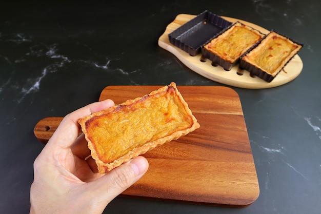 Man's hand holding a fresh baked pumpkin tartlet placing on the wooden breadboard