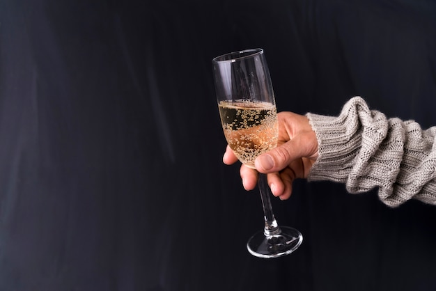 Man's hand holding glass of champagne against black background