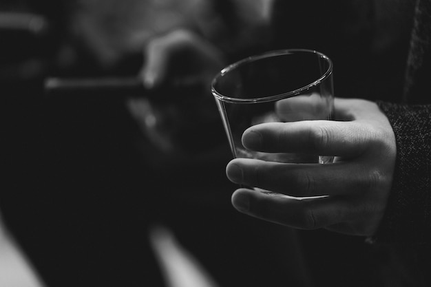 Man's hand holding glass of whiskey. black and white