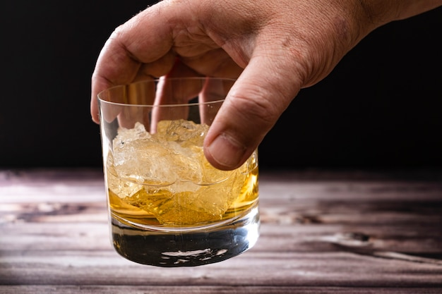 A man's hand holding a glass with whiskey or scotch and large chunks of ice on a rustic wooden table
