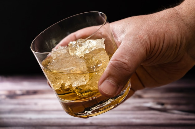 A man's hand holding a glass with whiskey or scotch and large pieces of ice from a rustic wooden table