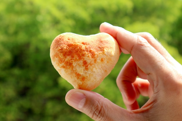 Man's hand holding a heart shaped homemade pao de queijo or brazilian cheese bread with blurry green foliage in background