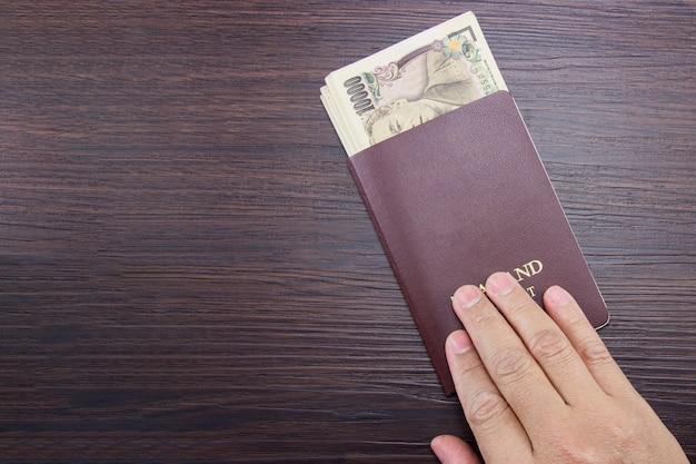 茶色の暗い木製のテーブルに国際パスポートと日本のお金を持っている男の手。