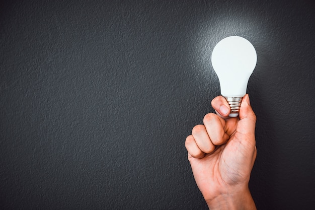 Man's hand holding led light bulb  over black wall