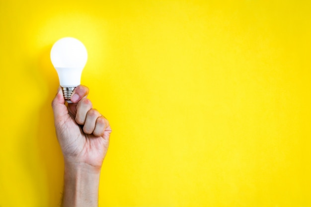 Man's hand holding led light bulb over yellow color