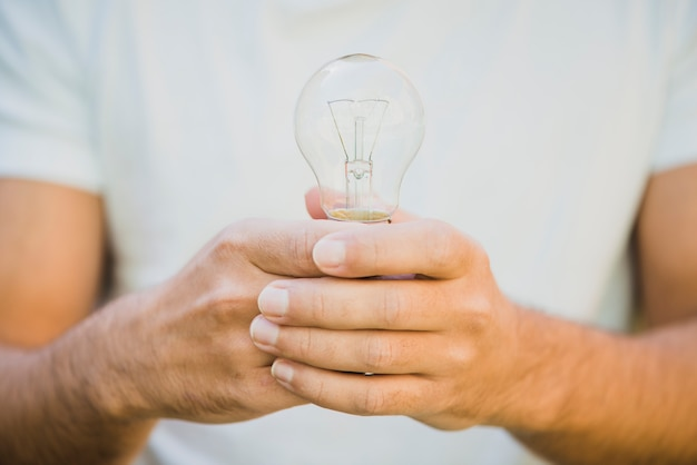 Man's hand holding light bulb