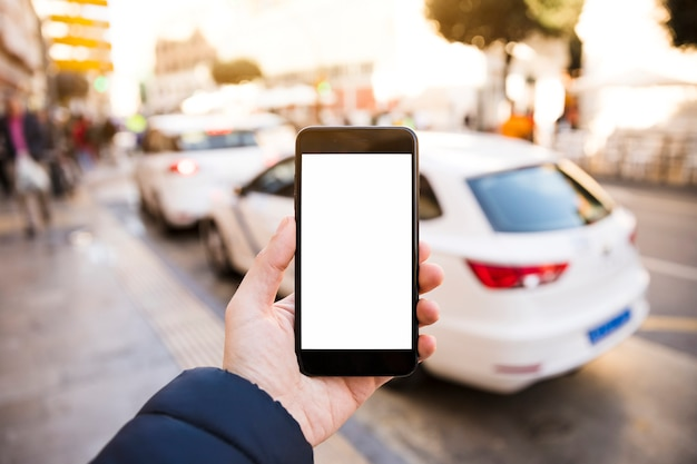 Man's hand holding mobile phone in front of traffic on road