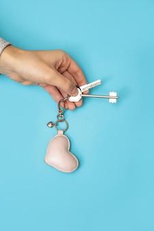 Рука человека держа новый ключ с сердцем от дома на сини.